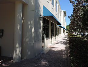 paved interconnected front porches for the executive suite offices of a business center with topiary and grass