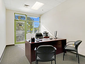 An executive suite office with a desk with three chairs, and a glass door and window to the street.
