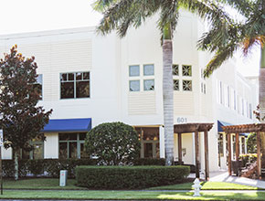The outside main entrance for a two story business center with some palm trees and overhangs